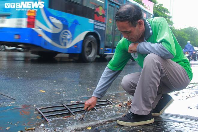 Tài xế xe ôm khơi thông cống thoát nước trên phố Hà Nội sau trận mưa lớn - 6