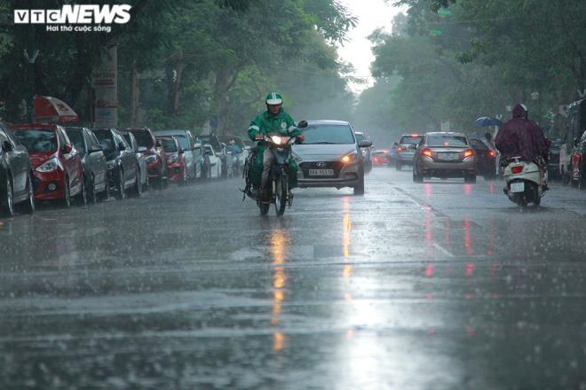 Tài xế xe ôm khơi thông cống thoát nước trên phố Hà Nội sau trận mưa lớn - 1