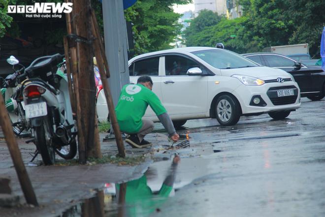 Tài xế xe ôm khơi thông cống thoát nước trên phố Hà Nội sau trận mưa lớn - 4