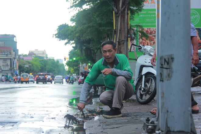 Tài xế xe ôm khơi thông cống thoát nước trên phố Hà Nội sau trận mưa lớn - 5
