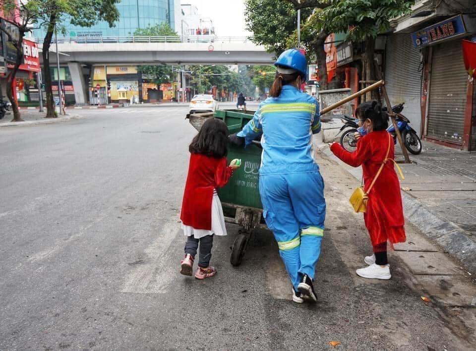 Hình ảnh đẹp ngày mùng 1 Tết: Hai bé gái xúng xính áo dài, tíu tít theo chân mẹ là công nhân môi trường đi làm - Ảnh 2.