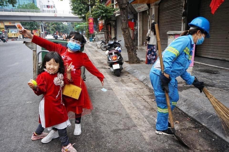 Hình ảnh đẹp ngày mùng 1 Tết: Hai bé gái xúng xính áo dài, tíu tít theo chân mẹ là công nhân môi trường đi làm - Ảnh 1.