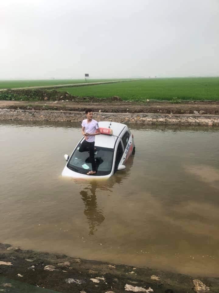 Taxi không rõ nguyên nhân nằm chìm dưới mương nước, tài xế loay hoay đạp cửa thoát ra ngoài - Ảnh 2.