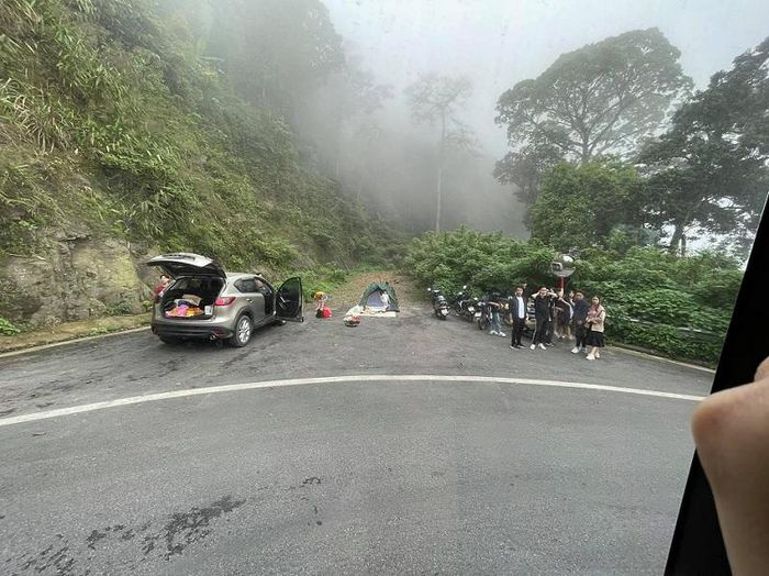 Nhóm du khách chụp ảnh, cắm trại ở ngay chỗ đường cứu nạn trên cung đường đèo dốc khiến ai cũng bức xúc - Ảnh 1.