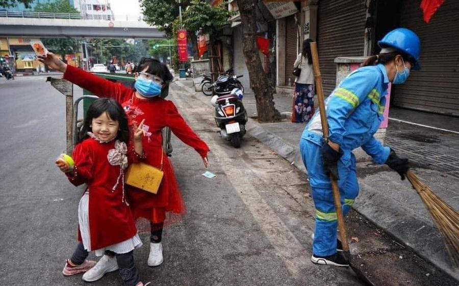 Hình ảnh đẹp ngày mùng 1 Tết: Hai bé gái xúng xính áo dài, tíu tít theo chân mẹ là công nhân môi trường đi làm