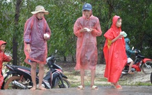 Người dân dầm mưa bên quốc lộ xin cứu trợ, giúp qua cơn đói ở Quảng Bình