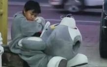 Bức ảnh chụp trộm cậu bé 9 tuổi đáng yêu mặc hình nộm ngồi bên vệ đường, khi tiết lộ về gia cảnh đã lập tức gây chú ý