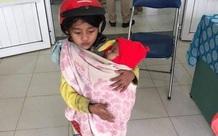 Bé gái 7 tuổi bế em đi tiêm phòng và câu chuyện phía sau khiến nhiều người xúc động